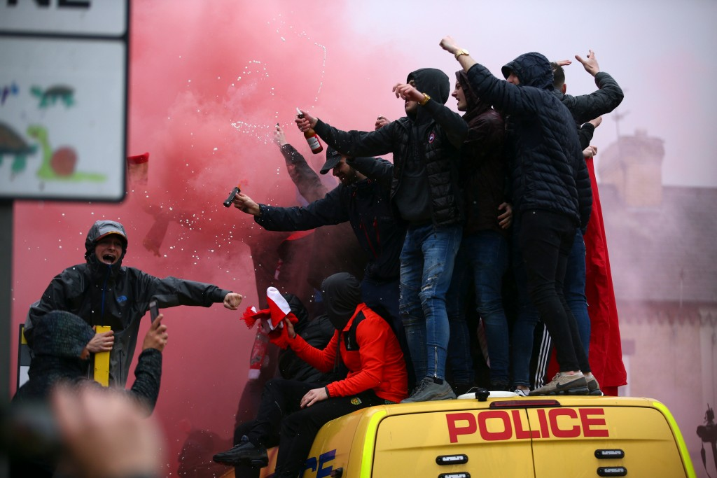 FILE - In this April 24, 2018 file photo, soccer fans stand on top of a police van amid smoke from flares outside the stadium before the Champions Lea...