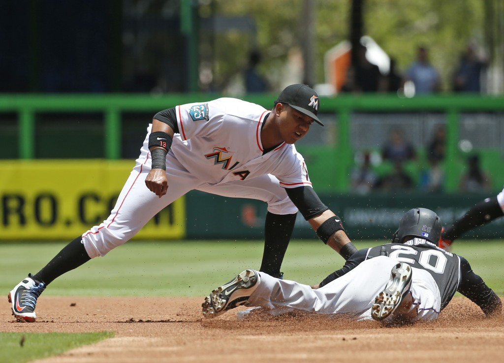 Miami Marlins second baseman Starlin Castro tags out Colorado Rockies' Ian Desmond after Desmond attempted to steal second base during the first innin...