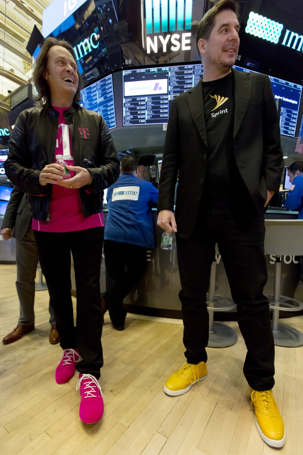 T-Mobile CEO John Legere, left, and Sprint CEO Marcelo Claure wear their signature color shoes on the floor of the New York Stock Exchange, Monday, Ap...