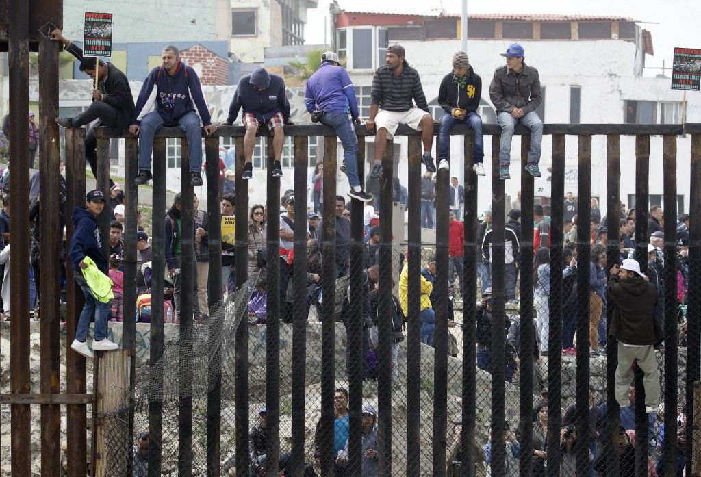 Central American migrants sit on top of the border wall on the beach during a gathering of migrants living on both sides of the border, Sunday, April ...