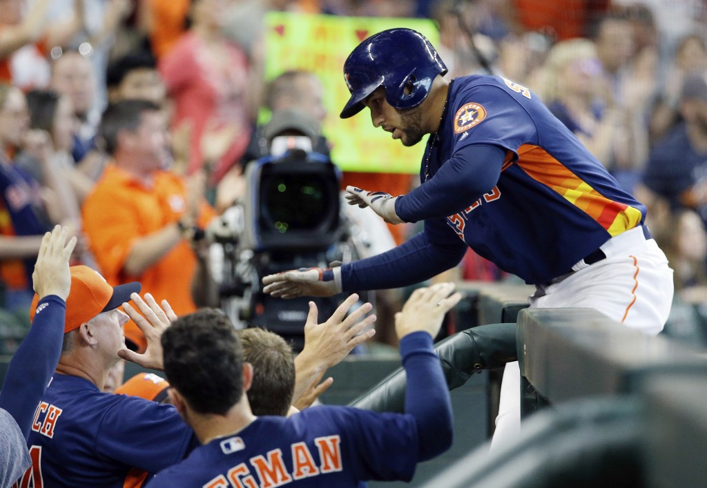 Houston Astros' George Springer, right, celebrates his home run in the dugout during the fifth inning of a baseball game against the Oakland Athletics...