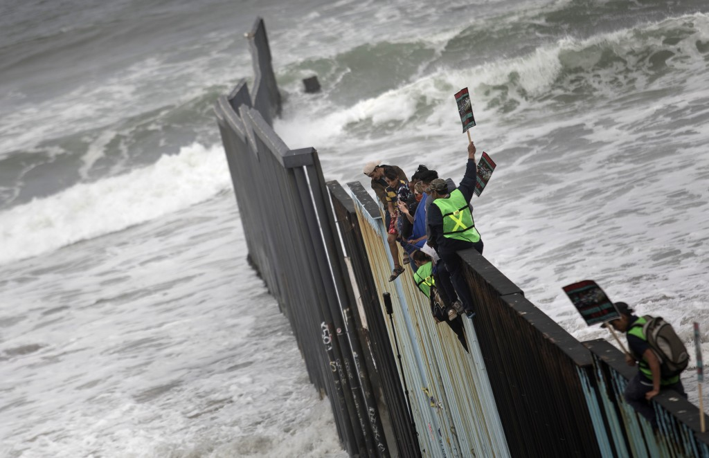 Central American migrants traveling with a caravan sit momentarily on top of the border wall during a gathering of migrants living on both sides of th...