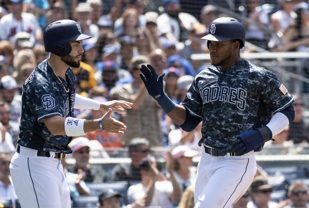 San Diego Padres' Eric Hosmer, left, and Franchy Cordero celebrate after they scored on a two-run single by Freddy Galvis during the third inning of a...