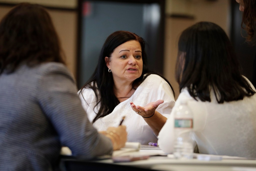 In this April 14, 2018 photo, Nelly Masa, who was displaced from her home in Puerto Rico, talks to paralegals during an event to help those affected b...