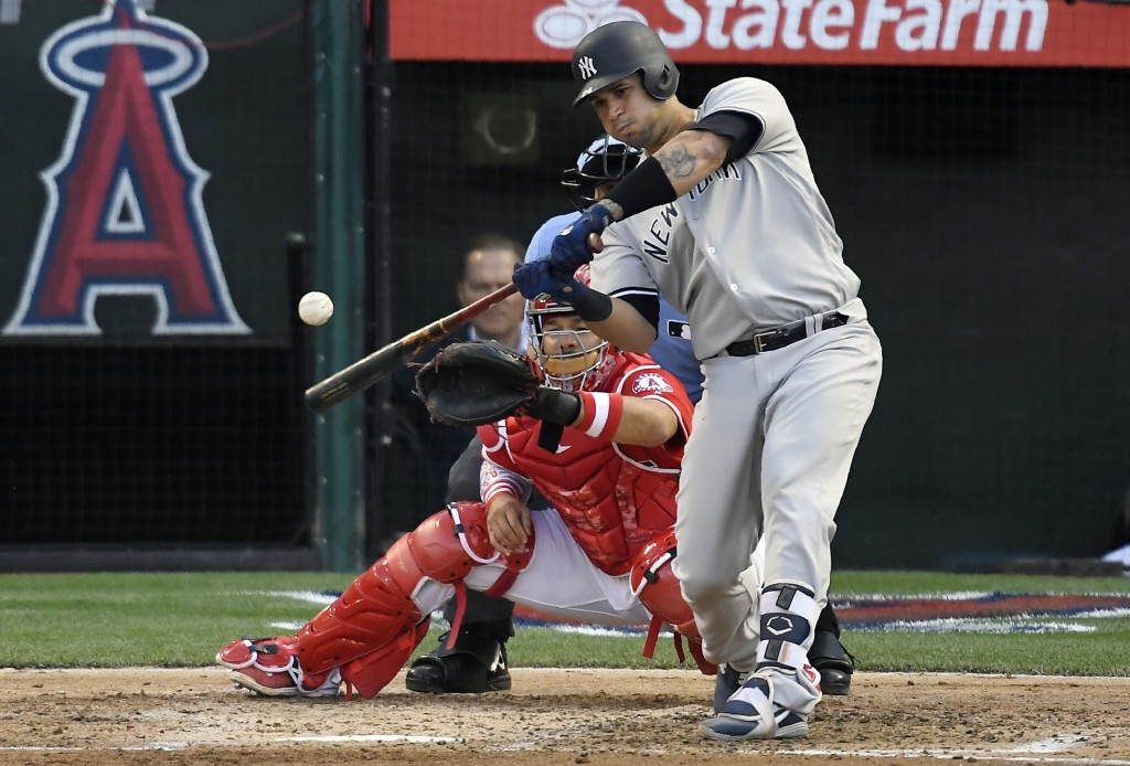 New York Yankees' Gary Sanchez, right, hits a two-run home run as Los Angeles Angels catcher Rene Rivera watches during the fourth inning of a basebal...