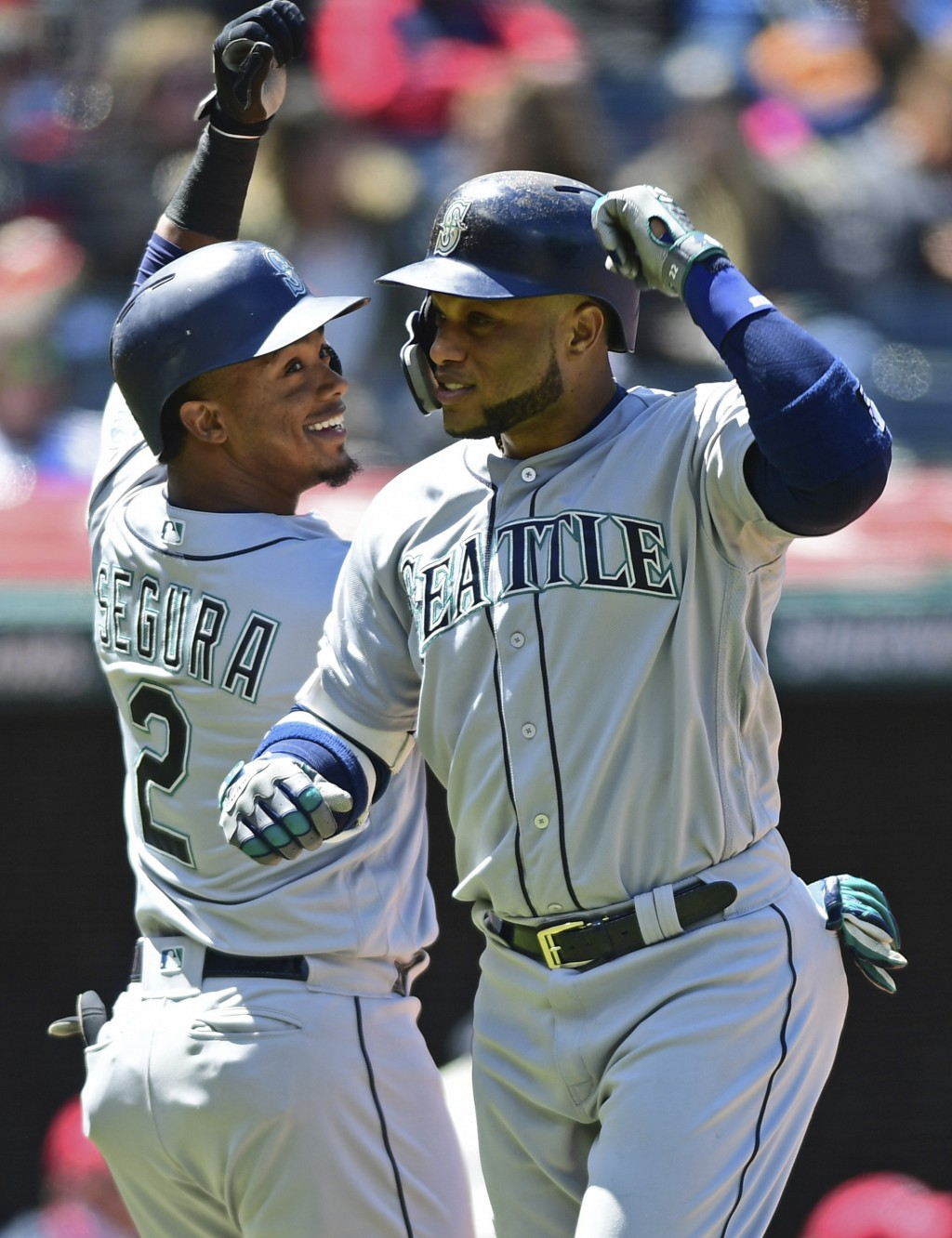Seattle Mariners' Robinson Cano, right, celebrates with Jean Segura after hitting a two-run home run off Cleveland Indians starting pitcher Josh Tomli...