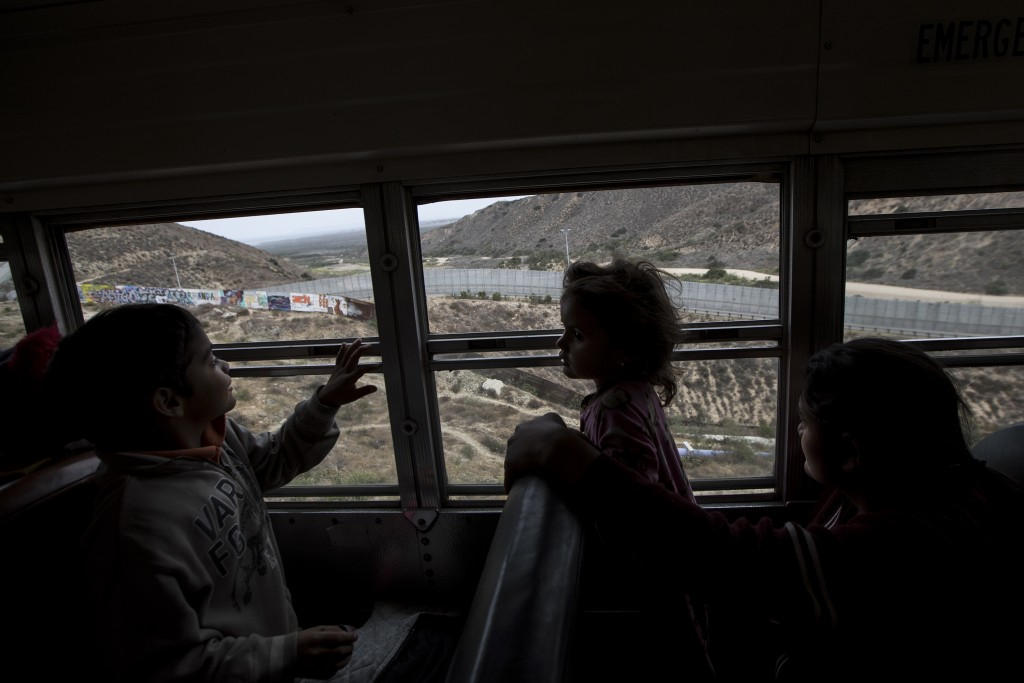 Central American children who are traveling with a caravan of migrants, look at the border wall from a bus carrying the group to a gathering of migran...
