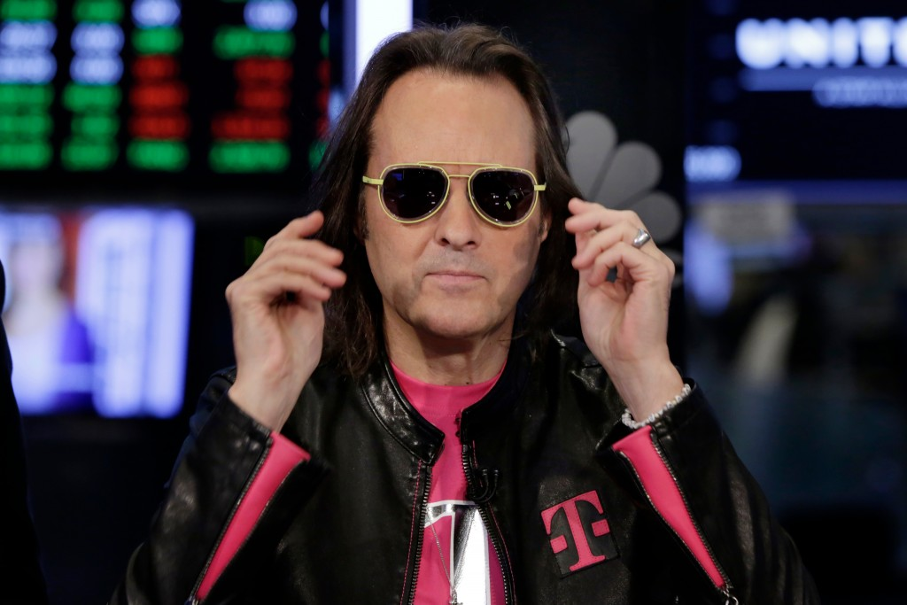 T-Mobile CEO John Legere wears Sprint-yellow sunglasses on the floor of the New York Stock Exchange, Monday, April 30, 2018. To gain approval for thei...