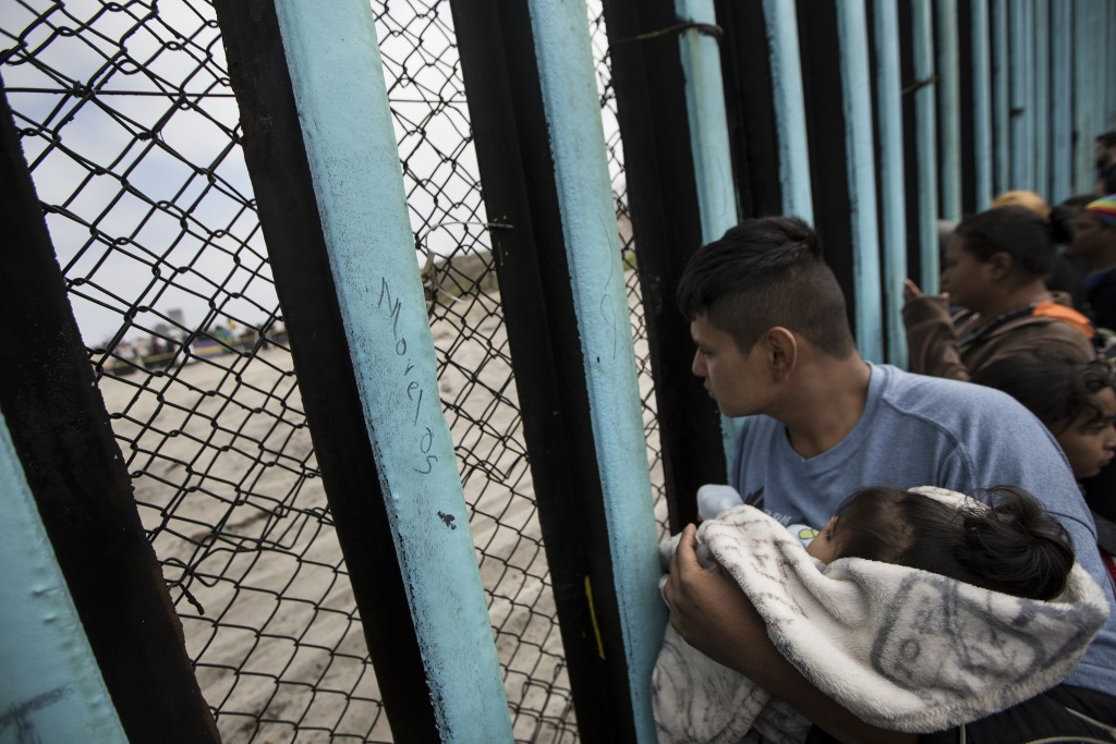 A member of the Central American migrant caravan, holding a child, looks through the border wall toward a group of people gathered on the U.S. side, a...