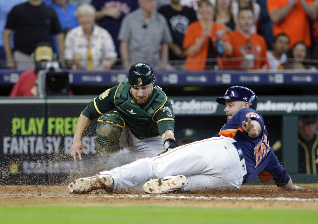 Houston Astros' catcher Brian McCann (16) is safe at the plate as Oakland Athletics' catcher Jonathan Lucroy (21) attempts the tag during the seventh ...