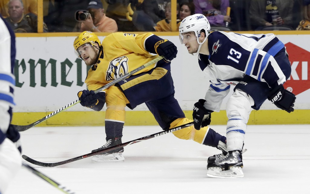 Nashville Predators left wing Viktor Arvidsson (33), of Sweden, shoots and scores a goal while defended by Winnipeg Jets' Brandon Tanev (13) during th...