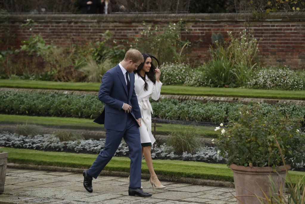 FILE - In this Nov. 27, 2017, file photo, Britain's Prince Harry and his fiancee Meghan Markle pose for photographers during a photocall in the ground...