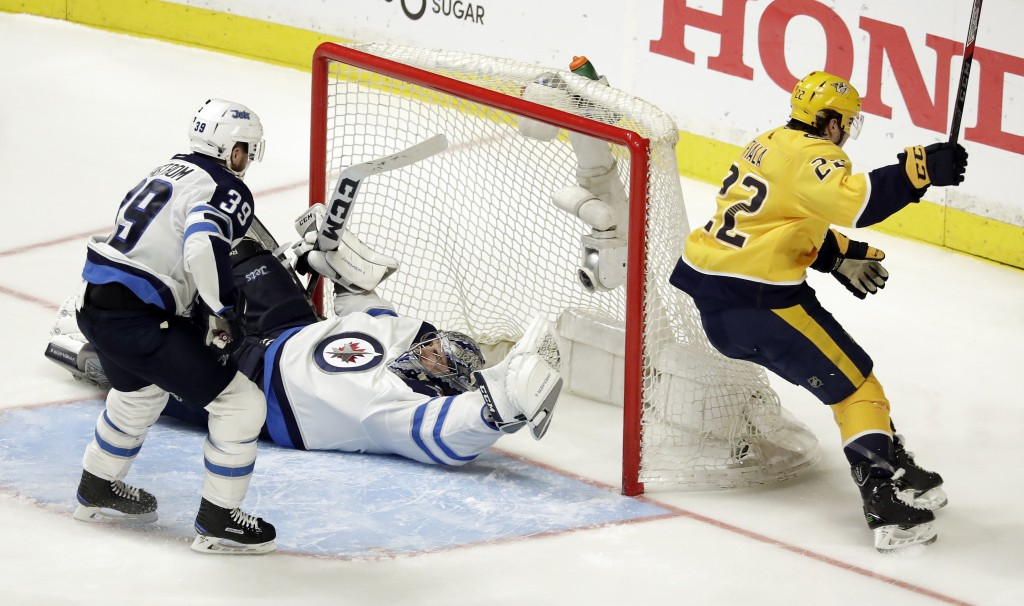 Nashville Predators left wing Kevin Fiala (22), of Switzerland, scores the winning goal against Winnipeg Jets goalie Connor Hellebuyck during the seco...