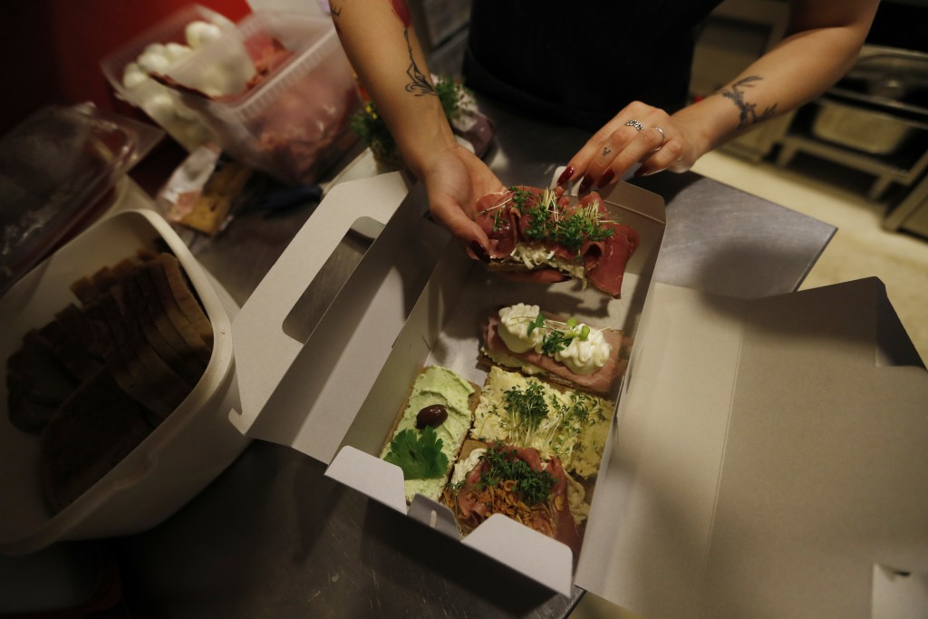 In this picture taken on Tuesday, April 10, 2018, woman prepares open-face sandwiches at bistro Sisters in Prague, Czech Republic. With an undying pop...