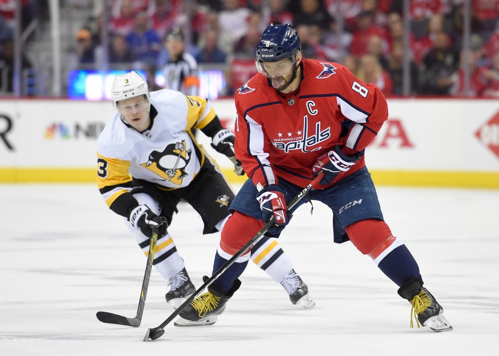 Washington Capitals left wing Alex Ovechkin (8), of Russia, skates with the puck in front of Pittsburgh Penguins defenseman Olli Maatta (3) during the...