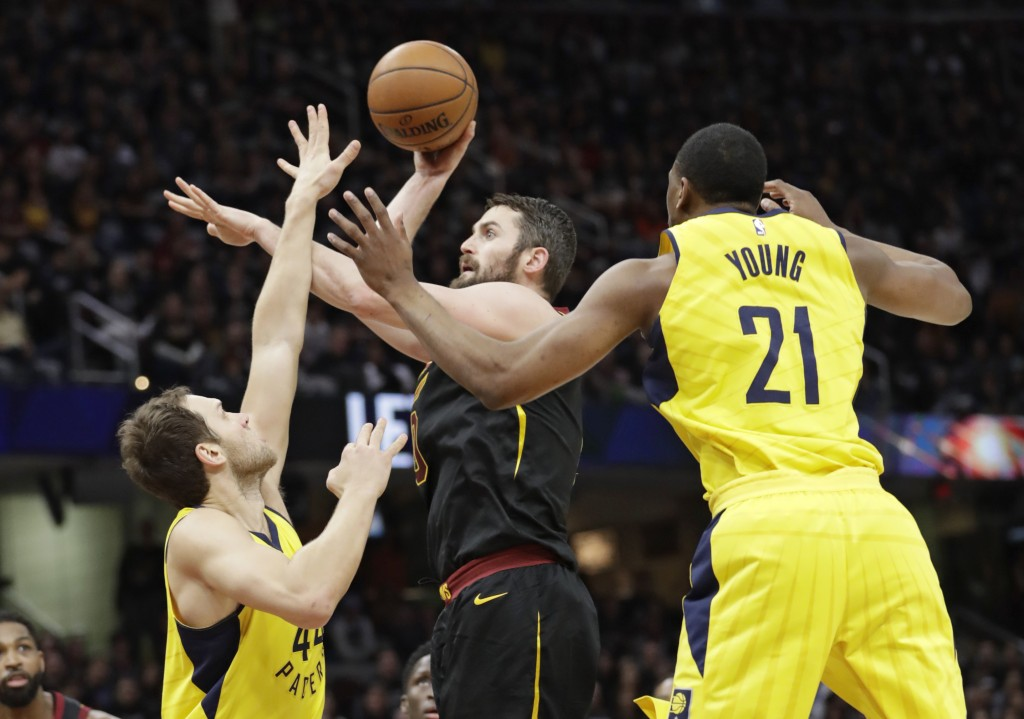 Cleveland Cavaliers' Kevin Love, center, shoots between Indiana Pacers' Bojan Bogdanovic, left, from Croatia, and Thaddeus Young in the first half of ...