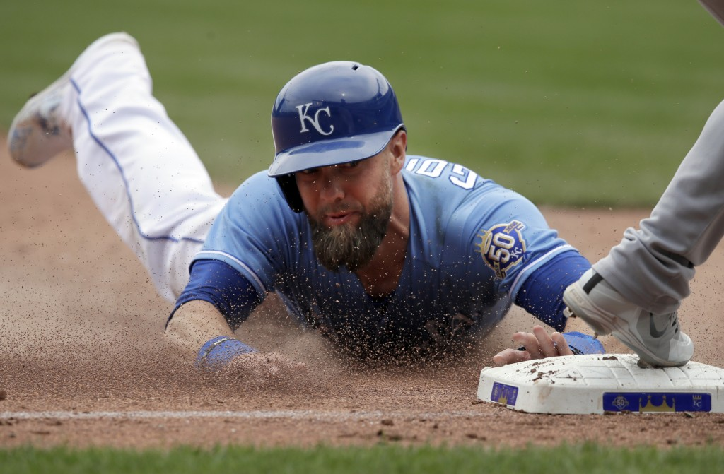 Kansas City Royals' Alex Gordon slides into third base during the sixth inning of a baseball game against the Chicago White Sox at Kauffman Stadium in...