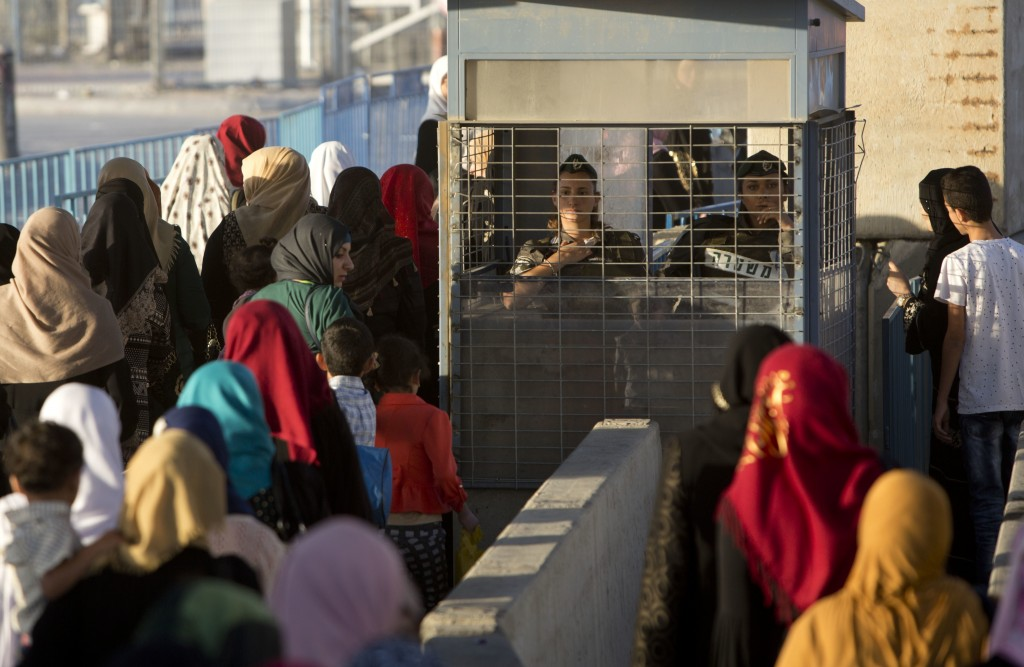 File - In this Palestinian Friday, June 24, 2016 file photo, women walk through cement blocks at an Israeli checkpoint on their way to attend the thir...