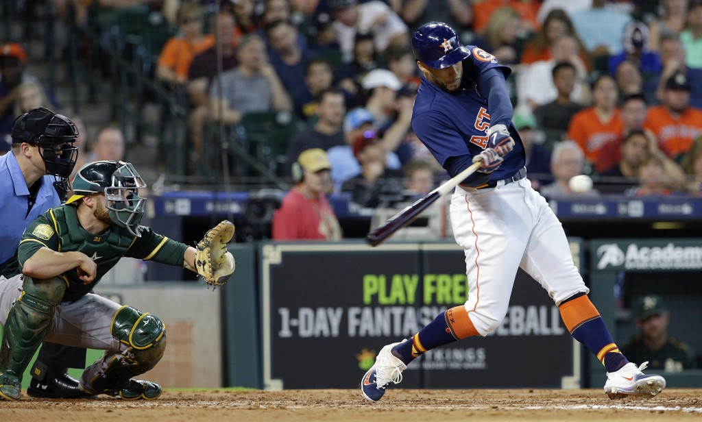 Houston Astros' right fielder George Springer, right, hits a home run during the fifth inning of a baseball game against the Oakland Athletics, Sunday...