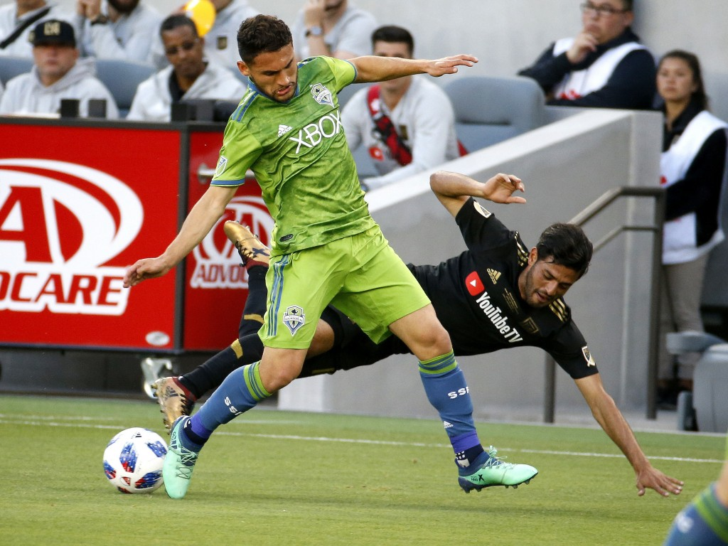 Seattle Sounders midfielder Cristian Roldan (7) vies for the ball with Los Angeles FC forward Carlos Vela (10) of Mexico, in the first half of an MLS ...
