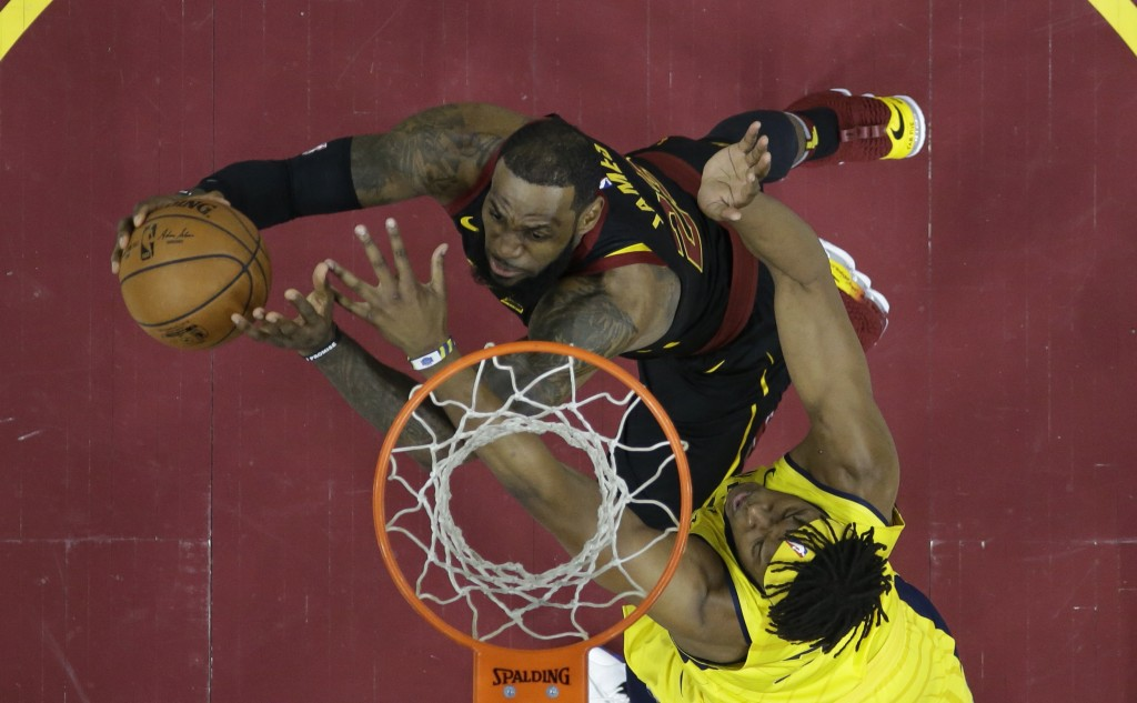 Cleveland Cavaliers' LeBron James, left, drives to the basket against Indiana Pacers' Myles Turner in the first half of Game 7 of an NBA basketball fi...
