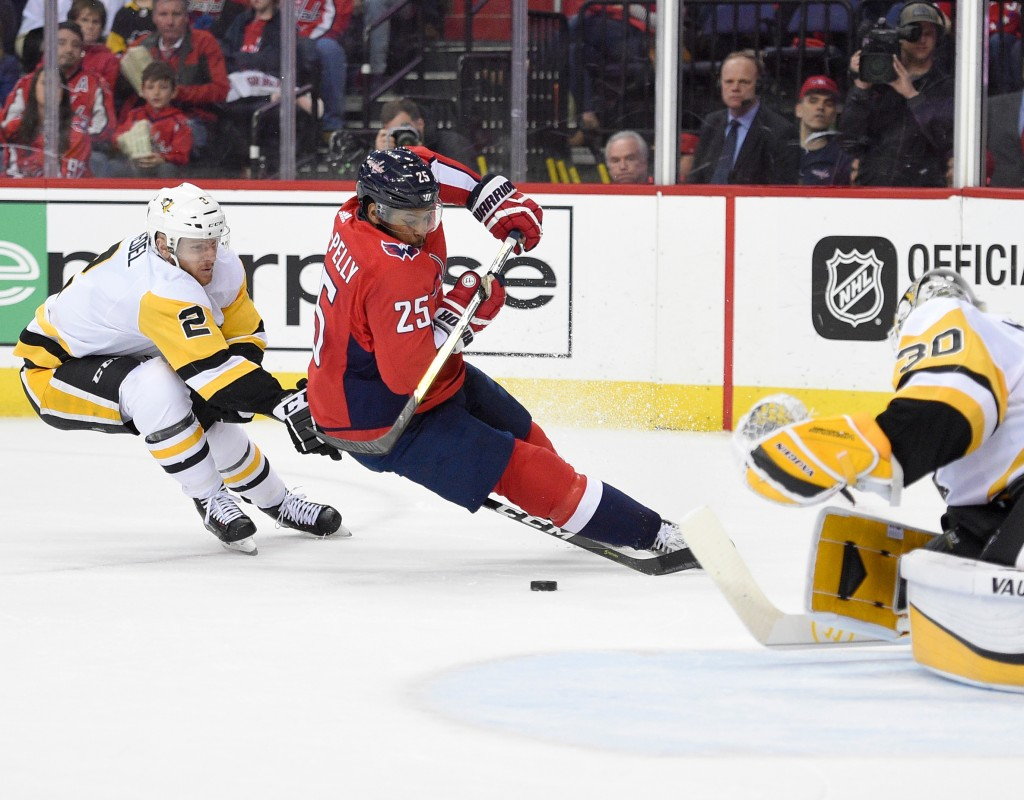 Washington Capitals right wing Devante Smith-Pelly (25) gets tripped up by Pittsburgh Penguins defenseman Chad Ruhwedel (2) and goaltender Matt Murray...