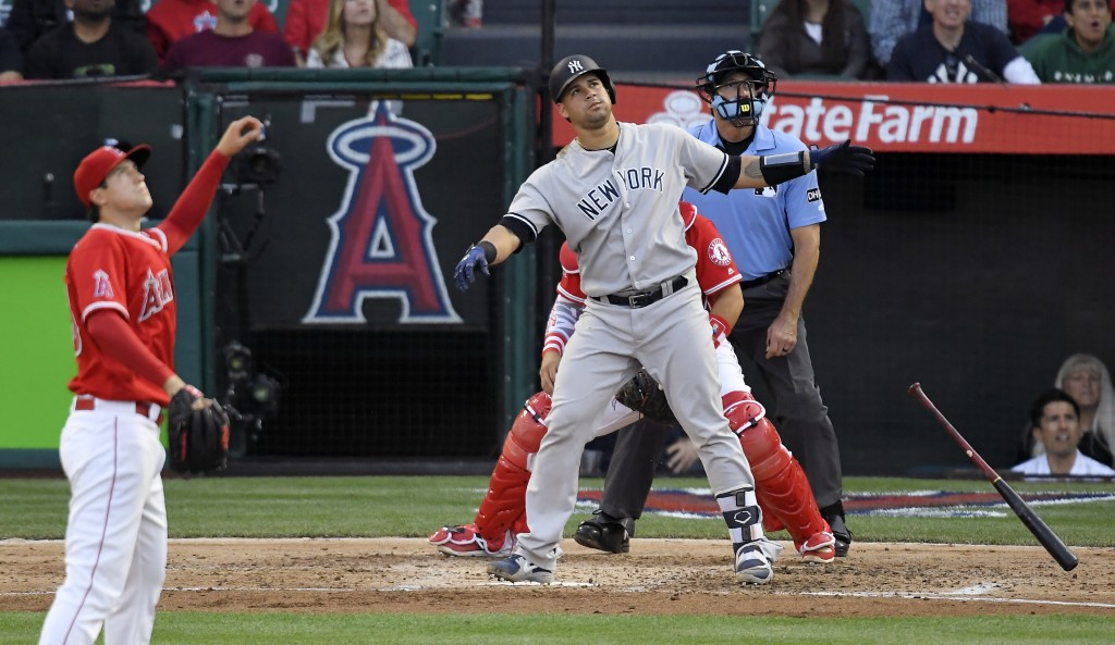 New York Yankees' Gary Sanchez, center, watches his two-run home run along with Los Angeles Angels starting pitcher Tyler Skaggs, left, and home plate...
