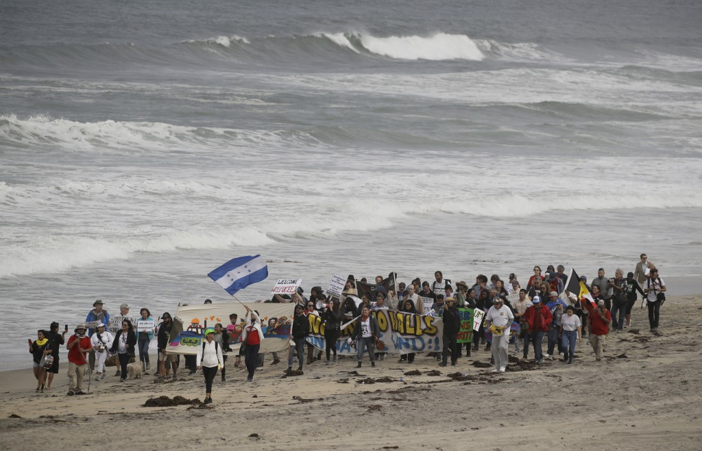 Demonstrators march to meet Central American migrants traveling in a caravan for a gathering at the border on the beach where the border wall ends in ...