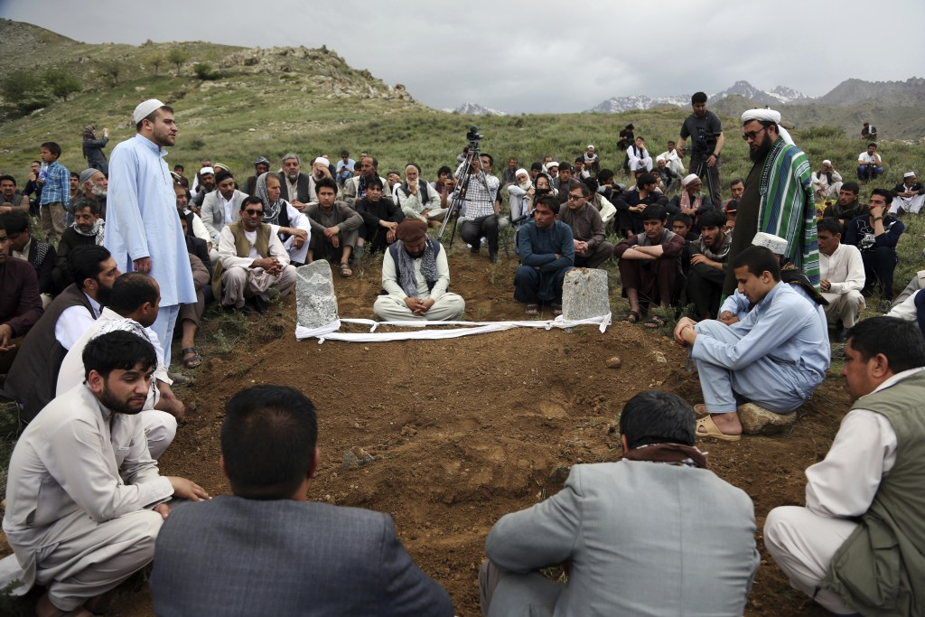 Relatives, colleagues and friends pray next to the grave of AFP chief photographer, Shah Marai, who was killed in today's suicide attacks, in Guldara,...