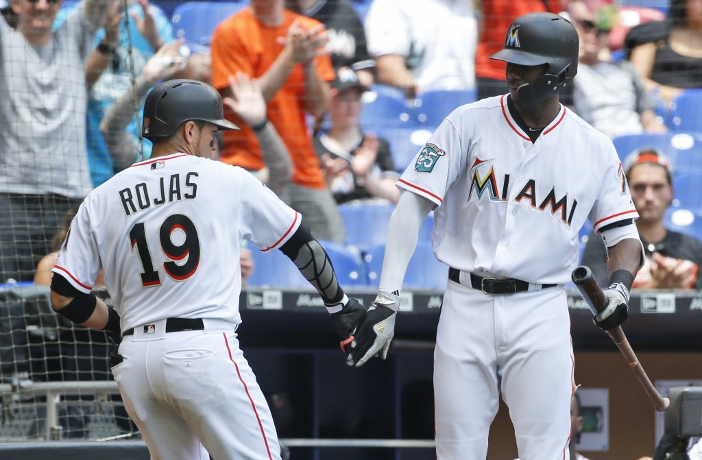 Miami Marlins' Miguel Rojas (19) is congratulated by Lewis Brinson after Rojas hit a home run during the fourth inning of a baseball game against the ...