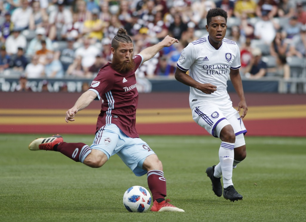 Colorado Rapids midfielder Enzo Martinez, front, takes a shot on the net as Orlando City midfielder Cristian Higuita pursues in the first half of an M...