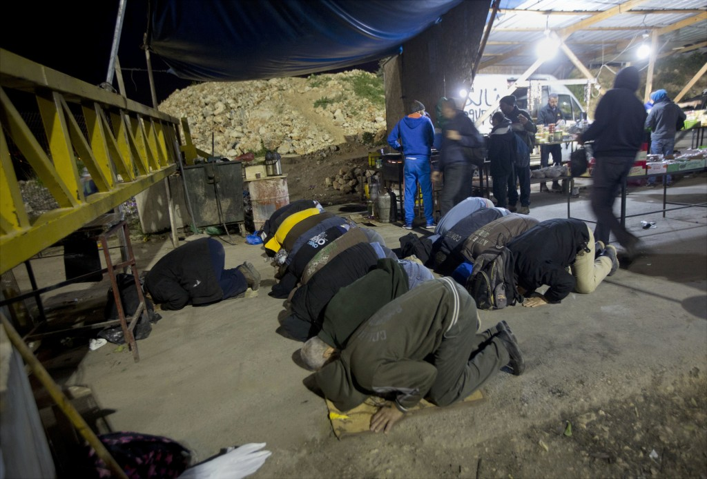 In this March 9, 2017 file photo, Palestinian laborers who work in Israel pray at a checkpoint before crossing into Israel, near the West Bank village...