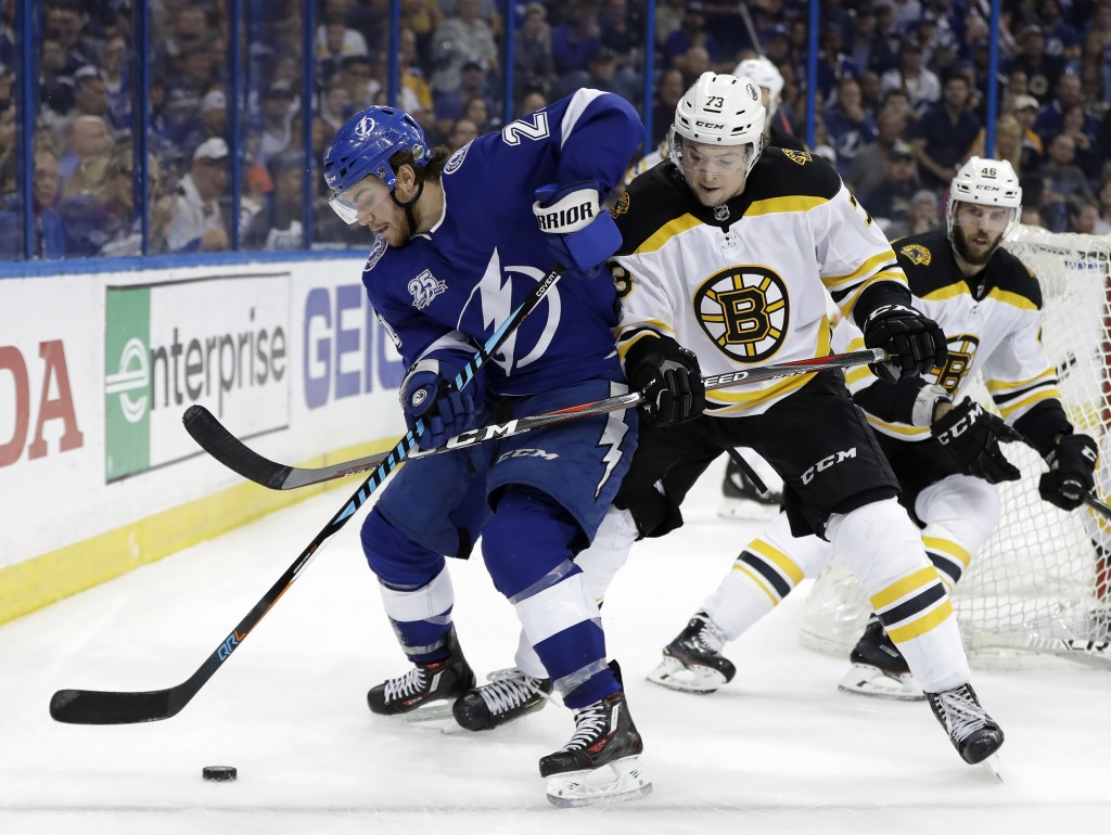 Tampa Bay Lightning center Brayden Point (21) gets tied up by Boston Bruins defenseman Charlie McAvoy (73) as they chase a loose puck during the secon...