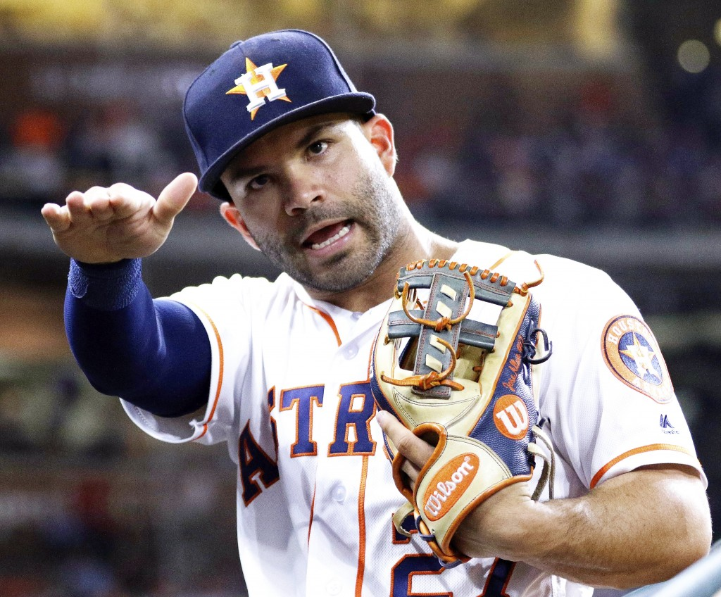 After throwing a ball to a fan, Houston Astros' second baseman Jose Altuve (27) tells the adult who grabbed it to give it to the kid next to him durin...