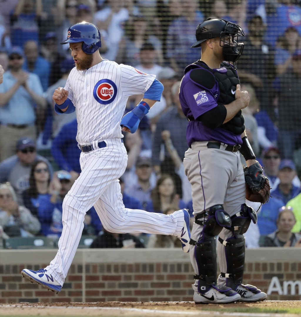Chicago Cubs' Ben Zobrist,left, scores past Colorado Rockies catcher Chris Iannetta off a single by Addison Russell during the first inning of a baseb...