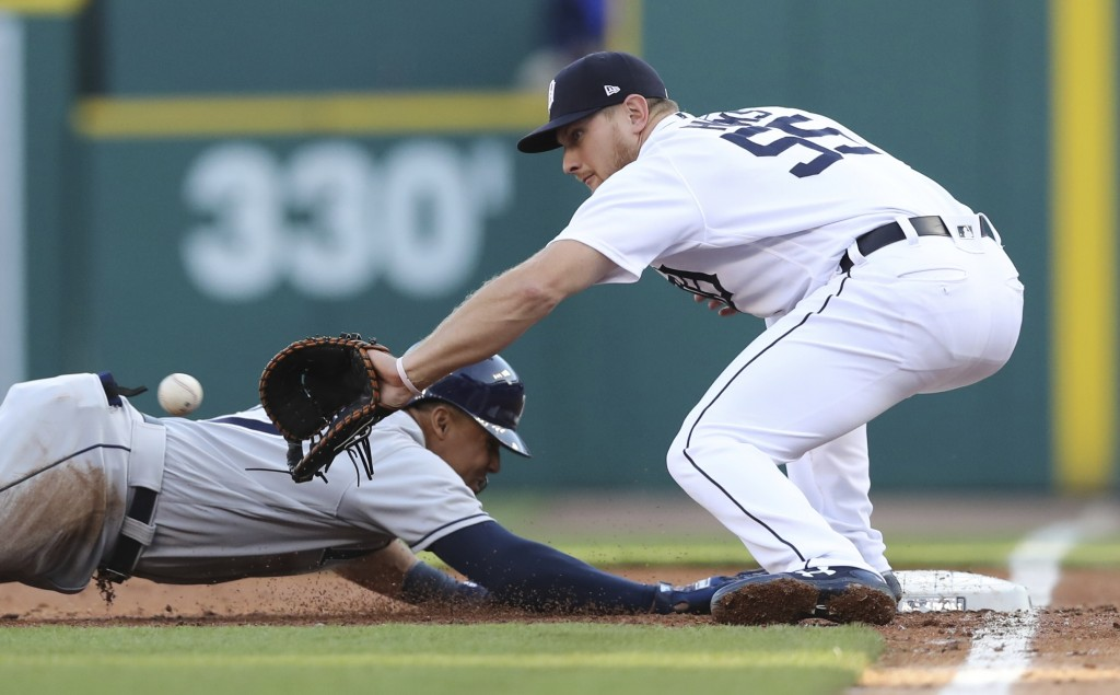 Tampa Bay Rays' Carlos Gomez safely jumps back to first as Detroit Tigers first baseman John Hicks waits on the throw during the second inning of a ba...