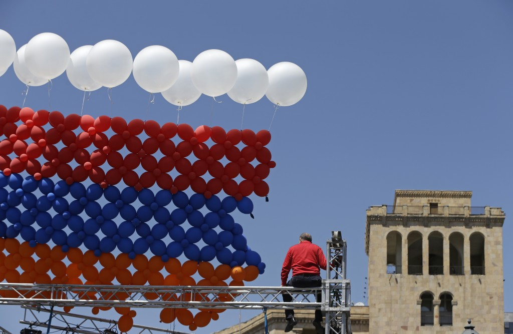 A man sits on top of the gantry of a stage during a break in a rally at the Republic square in Yerevan on Tuesday, May 1, 2018. Opposition lawmaker Ni...