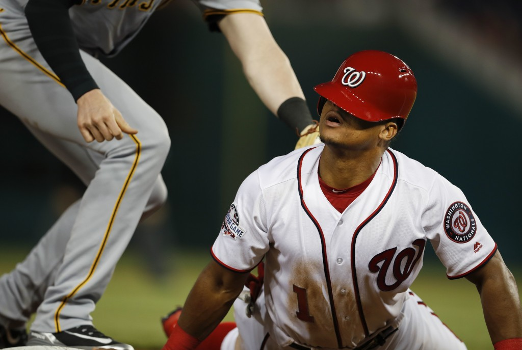 Washington Nationals' Wilmer Difo looks up after sliding back into third after a failed pick-off attempt by Pittsburgh Pirates third baseman Colin Mor...