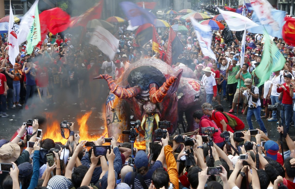 Protesters, mostly workers, burn an effigy depicting President Rodrigo Duterte as a devil, during a rally near the Presidential Palace at the global c...