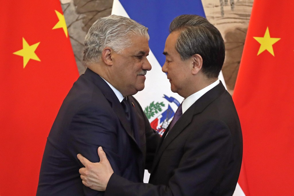 Dominican Foreign Minister Miguel Vargas, left, hugs with Chinese Foreign Minister Wang Yi after they signed the joint communique at the Diaoyutai Sta...