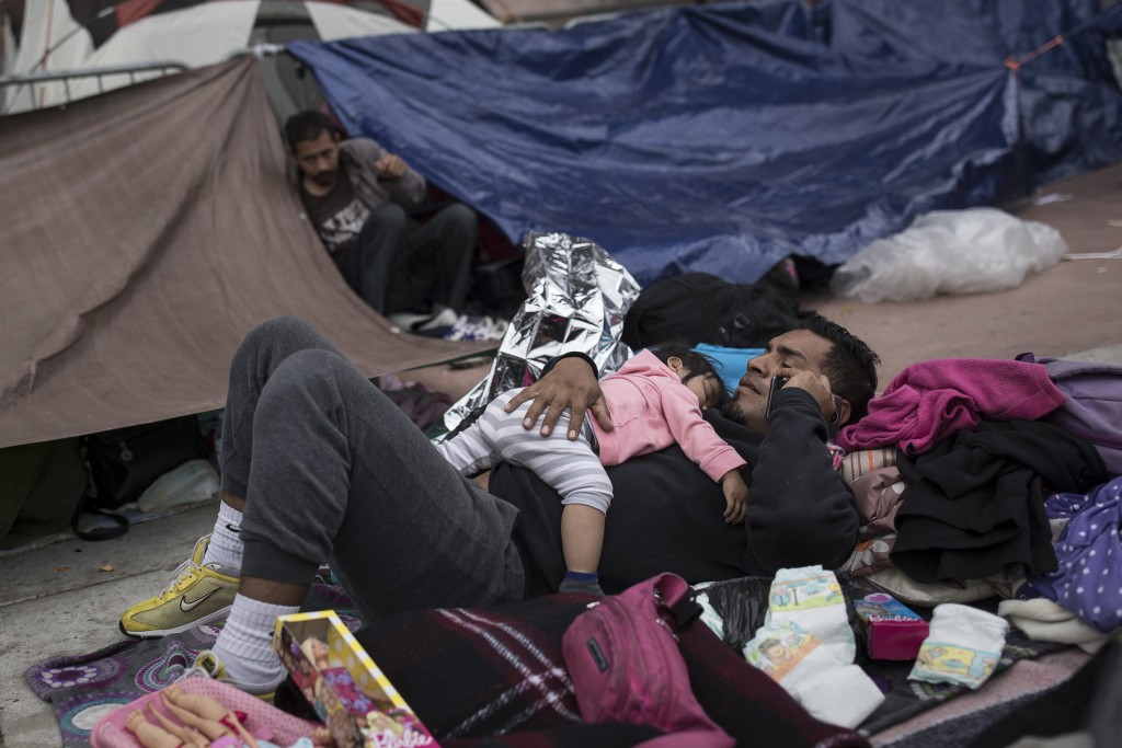 A migrant father and child, who traveled with the annual caravan of Central American migrants, rest where they set up camp to wait for access to reque...