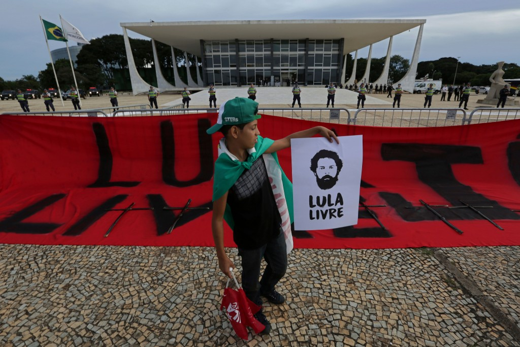 """FILE - In this April 17, 2018 file photo, a youth holds an image of Brazil's former President Luiz Inacio Lula da Silva that reads in Portuguese """"Free..."""