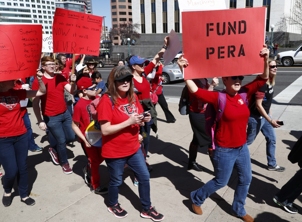 In this April 27, 2018, photograph, a teacher carries a placard in support of funding the teacher and other public sector workers' pension fund during...