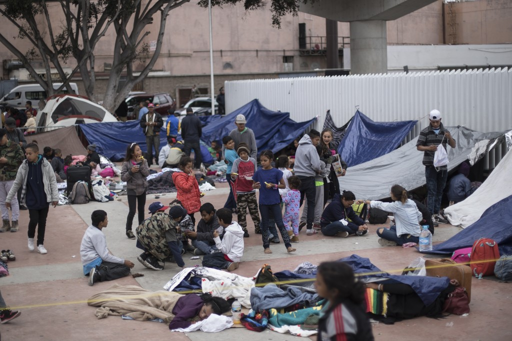 Migrants wait for access to request asylum in the US, at the El Chaparral port of Entry in Tijuana, Mexico, Monday, April 30, 2018. bout 200 people in...