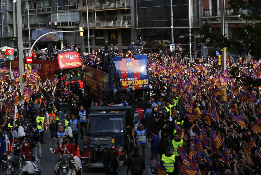 Barcelona's Gerard Pique, center, waves from a bus carrying the players celebrating during a street parade in Barcelona, Spain, Monday April 30, 2018,...