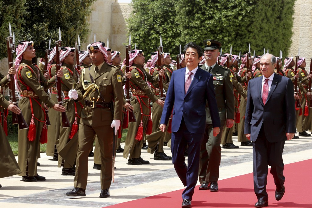 Japanese Prime Minister Shinzo Abe, left, arrives with Jordanian Prime Minister Hani Mulki, right, to meet King Abdullah at the Royal Palace in Amman,...