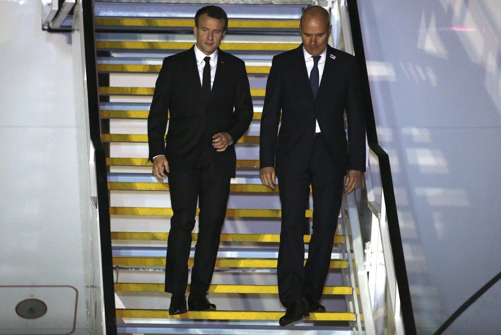 French President Emmanuel Macron, left, walks down the stairs with France's Ambassador to Australia Christophe Penot, as he arrives in Sydney, Tuesday...