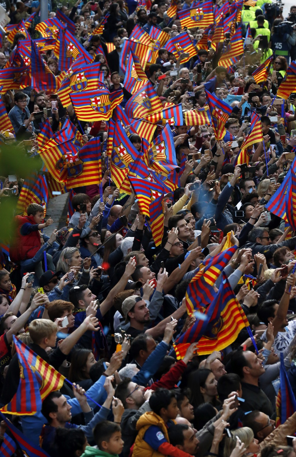 Barcelona fans take pictures of a bus carrying the players celebrating during a street parade in Barcelona, Spain, Monday April 30, 2018, after winnin...