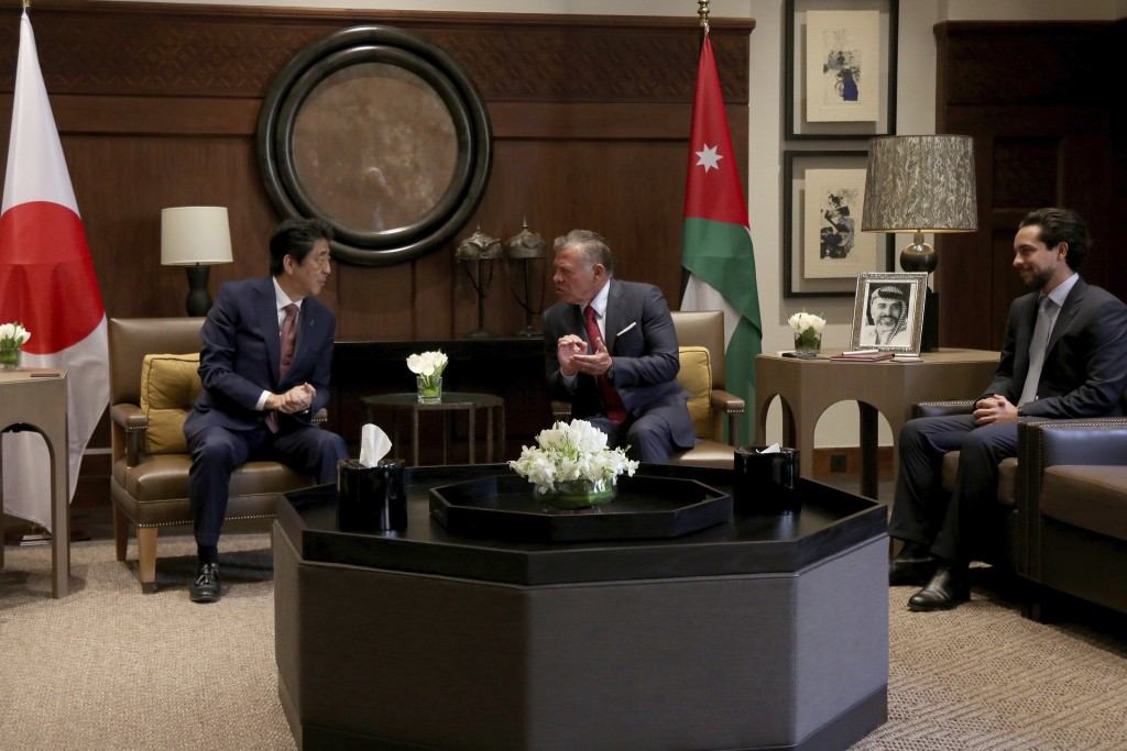 King Abdullah II of Jordan, centre, and Crown Prince Hussein, right, receive Japanese Prime Minister Shinzo Abe, at the Husseiniya palace in Amman, Jo...
