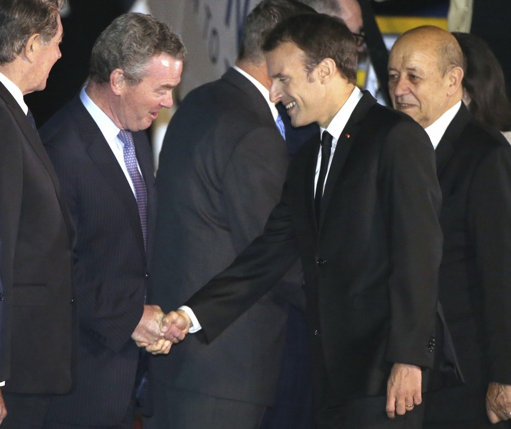 French President Emmanuel Macron, right, shakes hands with Australian Minister for Defense Industry, Christopher Pyne, as he arrives in Sydney, Tuesda...